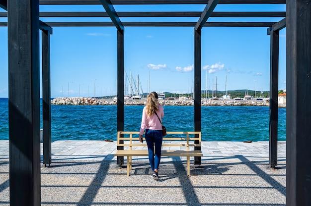 ギリシャ、ニキティのエーゲ海、黒い金属製の支柱とベンチのある桟橋の望楼で電話で話している女性