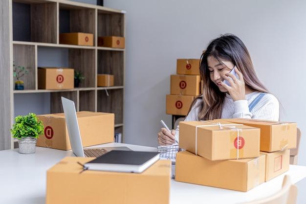 女性が電話で話し、ラップトップを使用してwebサイトで顧客からの注文を確認し、商品を小包に詰めて、民間の宅配会社に送ります。オンラインショッピングのコンセプト。