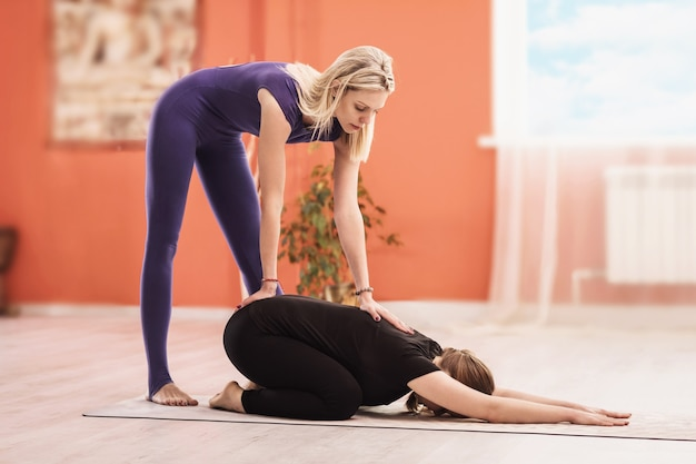 Преподаватель универсальной йоги выполняет тяговое растяжение позвоночника ученику, сидящему в детской позе баласана.