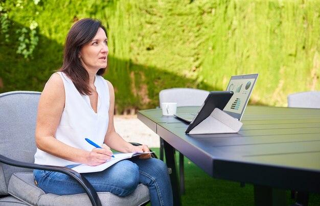 그녀의 노트북 태블릿을 사용하고 노트북에 메모를 하는 동안 야외 비즈니스 회의에서 재택 근무하는 여성