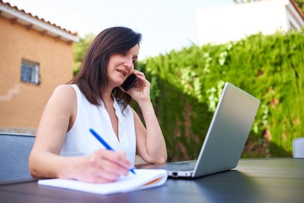 노트북으로 밖에서 재택근무를 하고 노트북으로 메모를 하는 동안 휴대전화로 통화하는 여성