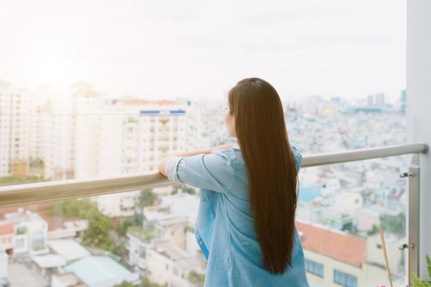 Женщина думает и смотрит на улицу из своего дома.