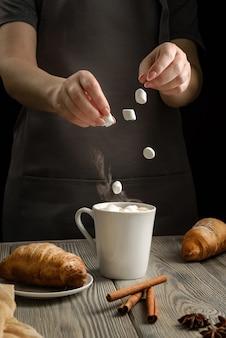 Женщина бросает зефир в чашку с какао.
