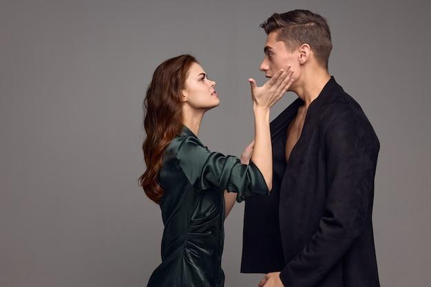 Женщина касается лица мужчины на сером фоне и становится напротив. фото высокого качества