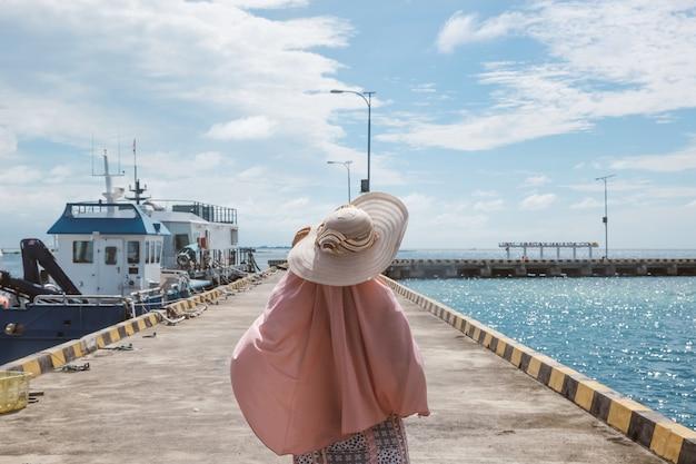 船が浮かんでいる港に立っている夏休みの女性観光客