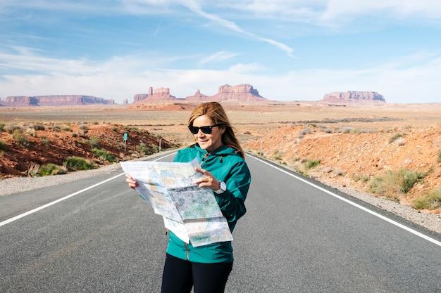 Женщина путешествует смотрящ карту на известном шоссе пустыни долины монументов в юте, сша.