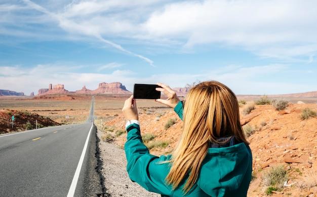Женщина совершает поездку по известному шоссе долины монументов в юте, сша.