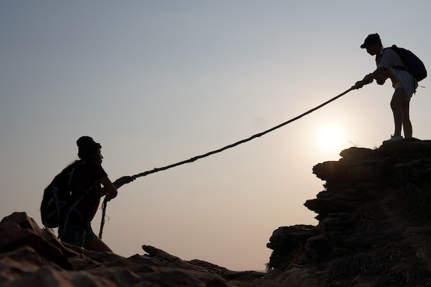 女性旅行者が友人を下からロープで引き上げます。成功、チームワーク、リーダーシップのためのアイデア。
