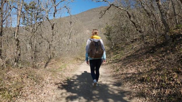 大きなバックパックを背負った女性旅行者が森の小道を歩きます。旅行とハイキングのコンセプト。 4k uhd