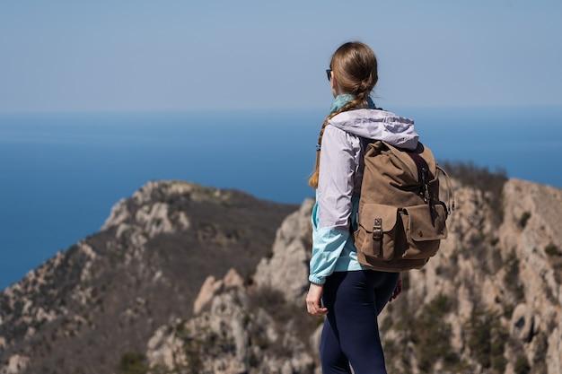 큰 등산가방을 메고 높은 산에 올라 아름다운 경치를 즐기는 여성 여행자...