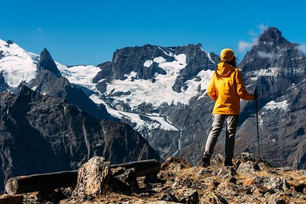 コーカサスを旅する女性。マウンテンスポーツ。アスリートハッピーフィニッシュ。マウンテンツーリズム。徒歩旅行。山への旅。山々の間を歩くノルディックウォーキング。コピースペース