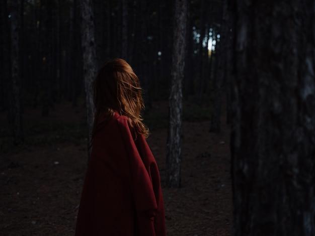 女性は夜、赤い格子縞を肩に乗せて森を旅します。高品質の写真