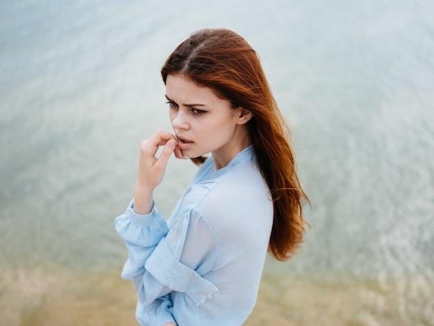 赤い髪の青いシャツを着て海の近くのビーチを旅する女性