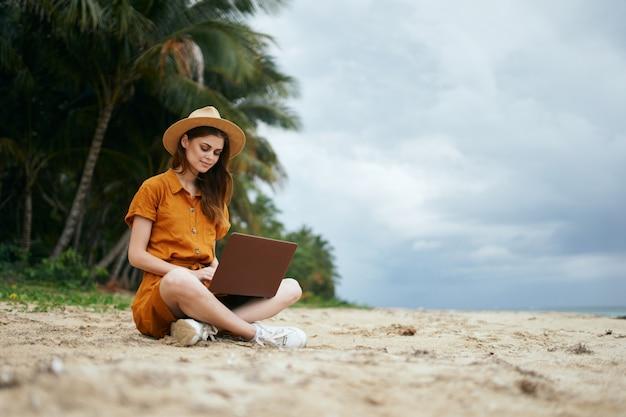 Женщина путешествует с ноутбуком вдоль океана по песку с пальмами