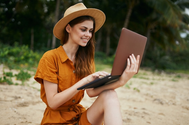 ヤシの木が砂に沿って海に沿ってラップトップを持って旅行する女性