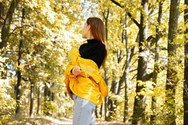 黄色い秋の森に背を向けた女性