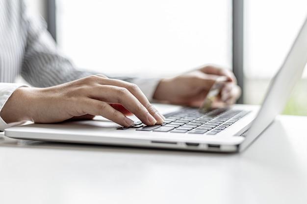 Женщина, печатающая на клавиатуре ноутбука, заполняет данные своей кредитной карты, чтобы оплатить заказ на сайте покупок в интернете. интернет-магазины и концепция оплаты кредитной картой.