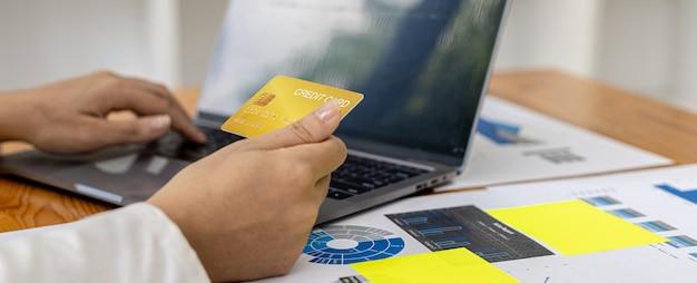 ノートパソコンのキーボードで入力している女性は、インターネットショッピングサイトで注文の支払いをするためにクレジットカード情報を入力しています。オンラインショッピングとクレジットカード決済のコンセプト。
