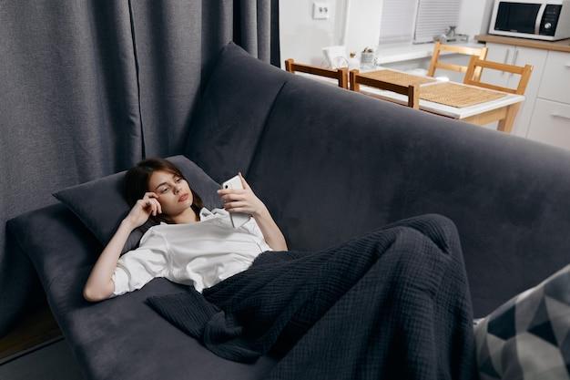 따뜻한 담요 아래의 여자는 소파와 백그라운드에서 창에 놓여 있습니다.