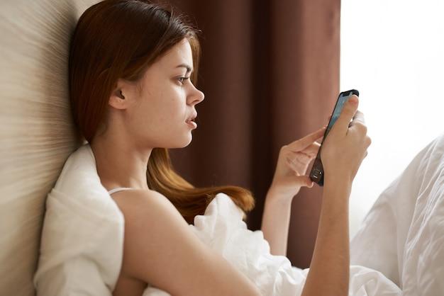 Женщина под одеялом лежит в постели и смотрит на экран мобильного телефона, вид сбоку