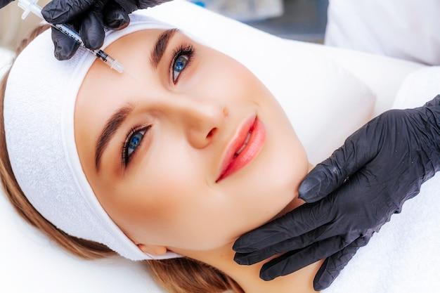 Женщина проходит у косметолога процедуру биоармирования лица. омоложение и лечение морщин.