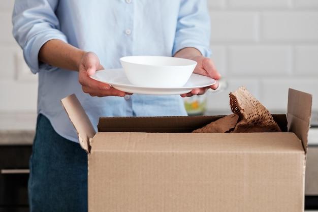 女性が新しい皿の入った箱を開梱します。