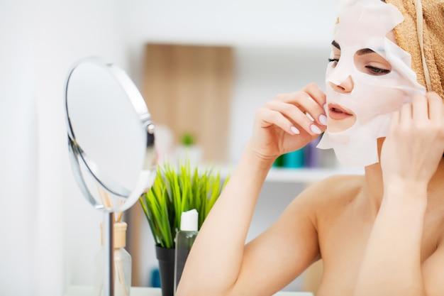 Женщина использует маску для ухода за лицом в ванной