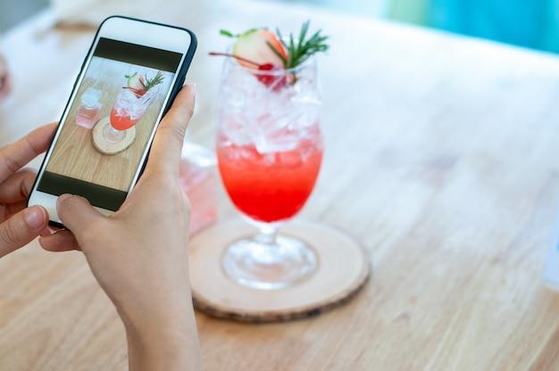 Женщина использует телефон, чтобы сфотографировать клубничный напиток в кафе, чтобы загрузить его в социальные сети. отдых в кафе