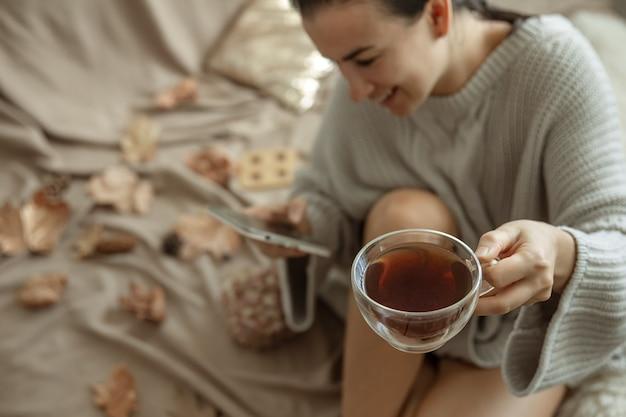 女性は電話を使用し、居心地の良いニットのセーター、ぼやけた背景でベッドに座っている間お茶を飲みます。