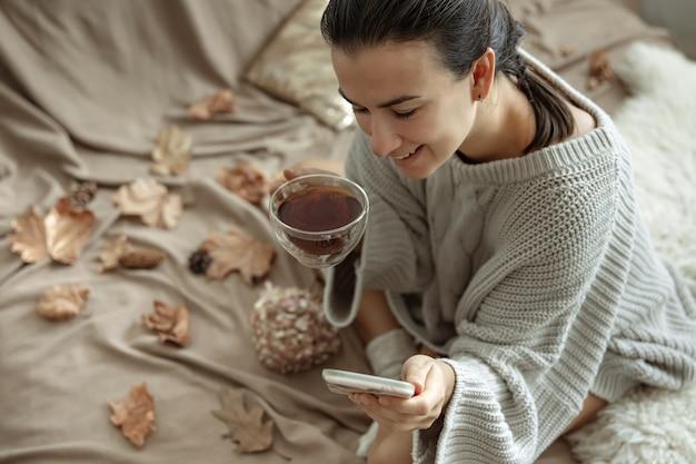 한 여성이 전화를 사용하고 아늑한 니트 스웨터를 입고 침대에 앉아 차 한 잔을 들고 있다