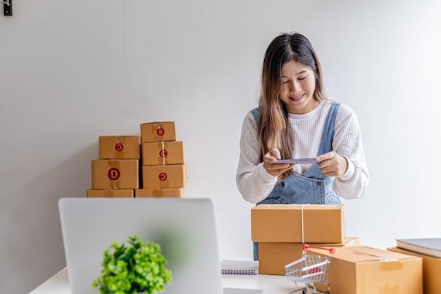 スマートフォンを使って小包箱、商品を梱包する小包箱の前で写真を撮り、民間の宅配会社を通じて商品を配達する女性。オンライン販売とオンラインショッピングの概念。