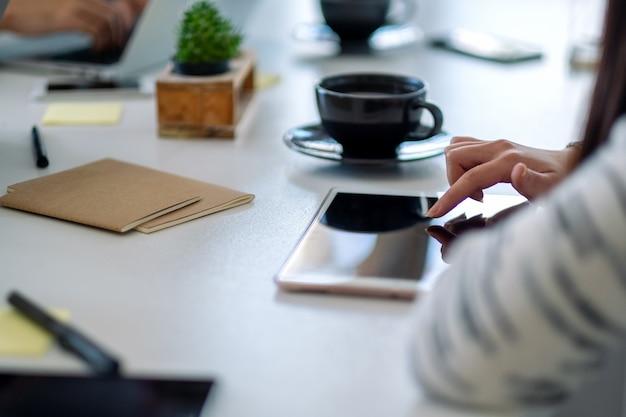 テーブルの上にコーヒーカップとタブレットpcを使用して指を指している女性
