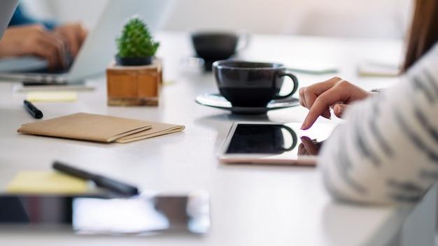테이블에 커피 컵이 있는 태블릿 pc를 사용하고 가리키는 여성