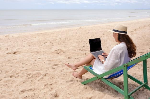 ビーチチェアに横になってラップトップコンピューターを使用して入力する女性