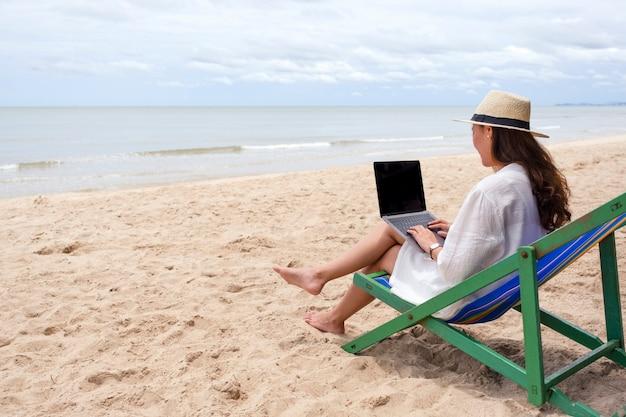 ビーチチェアに座ってラップトップコンピューターを使用して入力する女性