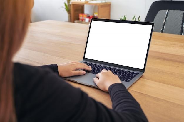 ラップトップを使用して、オフィスの木製のテーブルに空白の白いデスクトップ画面で入力する女性