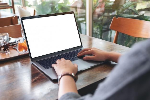 木製のテーブルに空白の白いデスクトップ画面でノートパソコンを使用して入力する女性