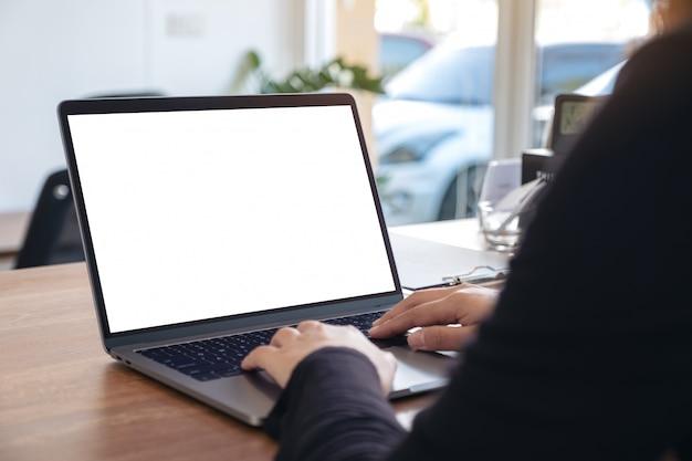 ラップトップを使用して、オフィスに座っているときに空白の白いデスクトップ画面で入力する女性