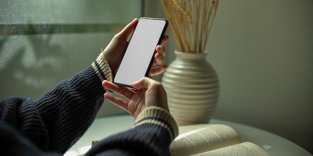 Женщина, используя смартфон во время чтения книги на журнальный столик с украшением следующего окна