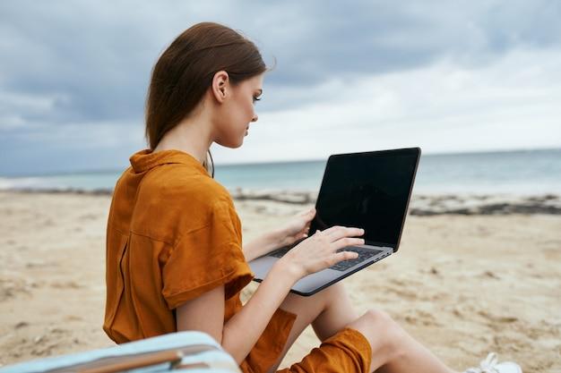 海を望むビーチでラップトップを使用している女性