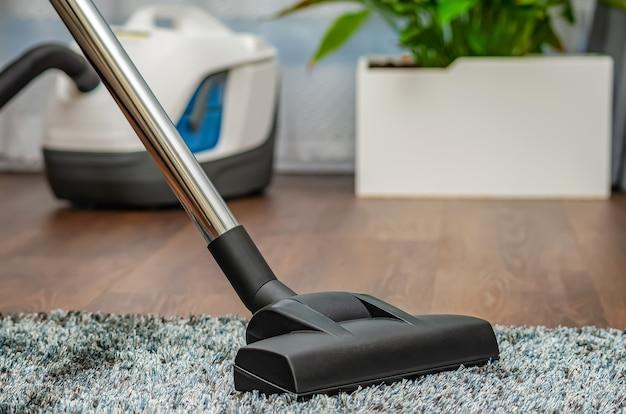 한 여성이 진공 청소기로 회색 카펫을 청소하고 있습니다. 청소 및 청결 개념입니다.