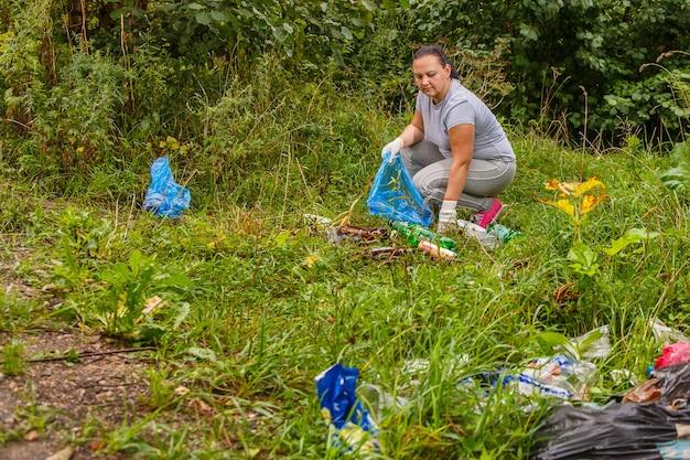 여성 자원 봉사자가 자연의 쓰레기통에서 쓰레기를 청소합니다.