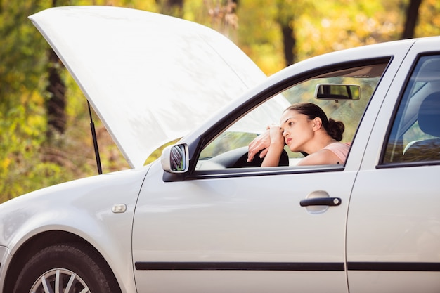 Женщина ждет помощи возле своей машины, разбитой на обочине