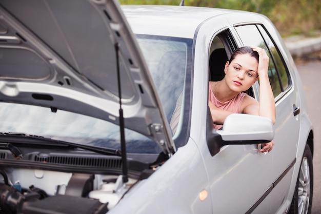 여자는 길가에서 고장난 차 근처에서 도움을 기다린다