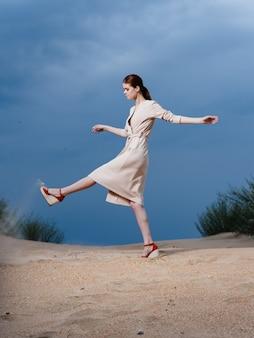 Женщина идет по пляжу в красных сандалиях широким шагом. фото высокого качества