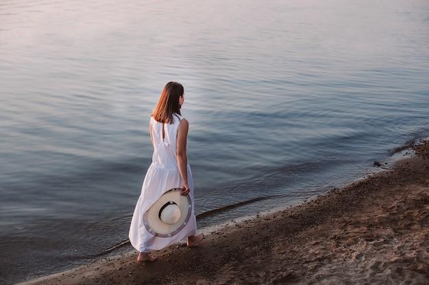 Женщина гуляет по пляжу в полный рост, вид сзади на молодую женщину в длинном белом платье и босиком ...