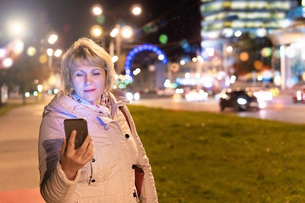 한 여성이 밤에 도시를 걷고 있습니다. 손에 전화기를 들고 있는 중년 여성이 보도에 있습니다.