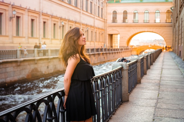 Женщина гуляет по летнему петербургу и остановилась на набережной.