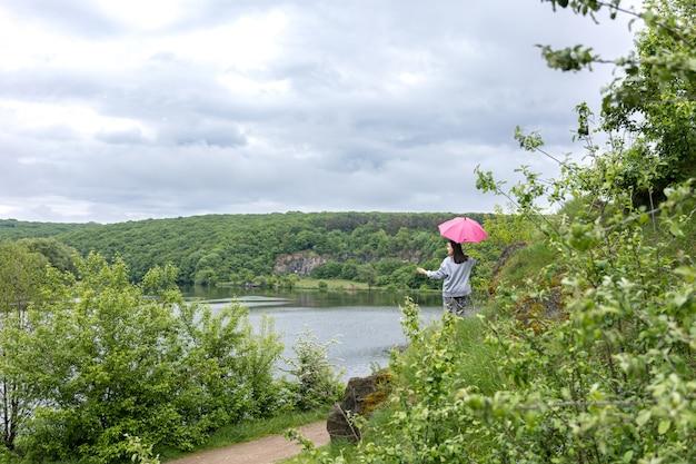 曇りの山岳地帯で傘の下を歩く女性