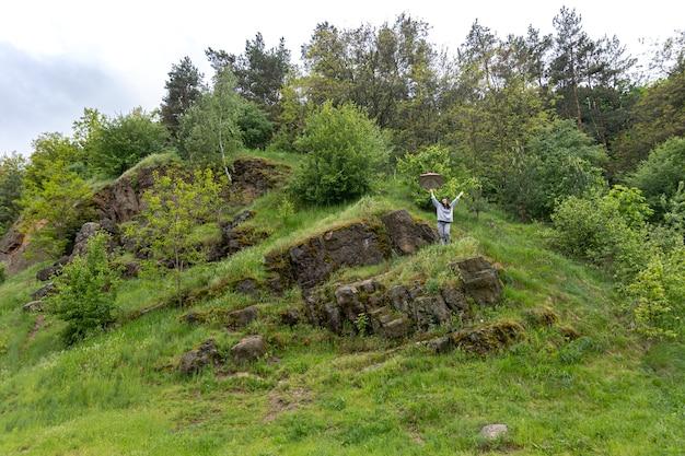 緑に覆われた岩の間、山の中の傘の下を歩く女性